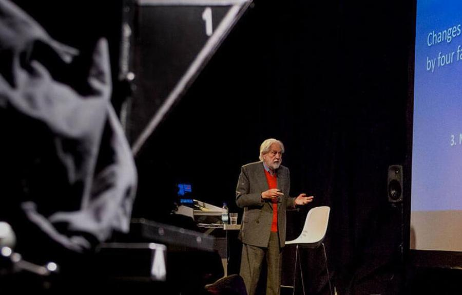 Lord David Puttnam delivers talk on stage, with filming equipment in foreground2