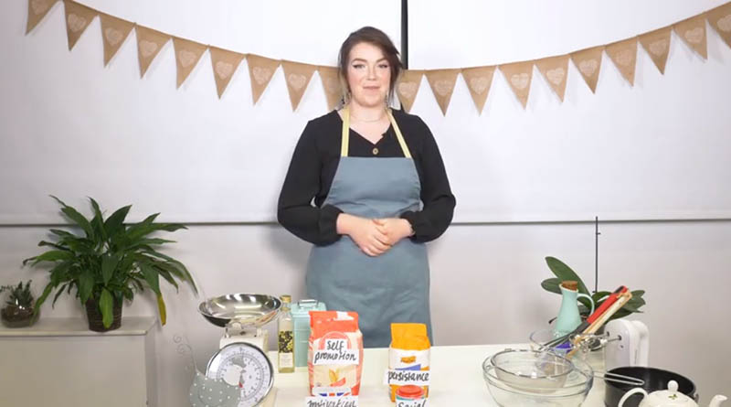 A woman wearing an apron and preparing to bake a cake2