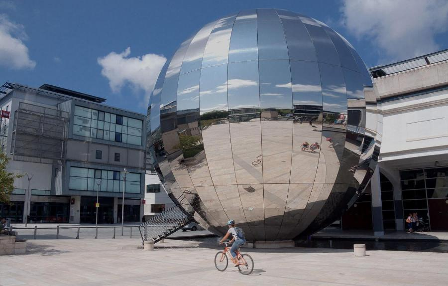 Large, reflective globe in a city space with cyclist out front2