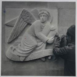 A black and white photo of a man with a chisel working on a wall sculpture of an angel