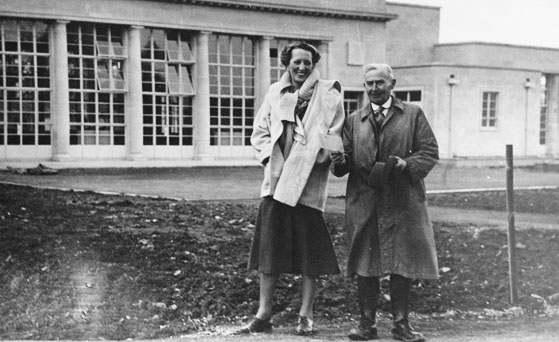 A black and white photo from the 1950s of a smiling woman and man standing in front of building with large windows
