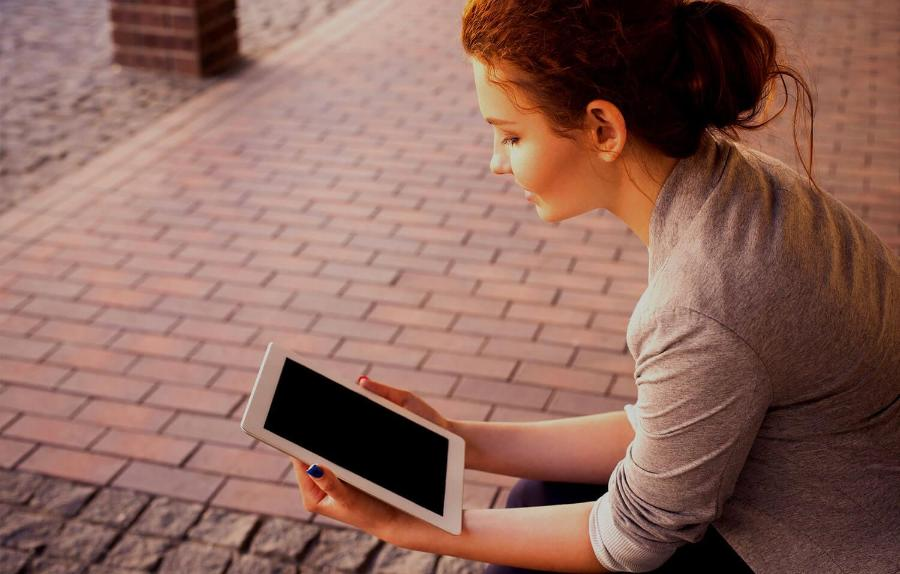 A woman with a blue painted nails holding and reading on an iPad tablet beside a pavement2