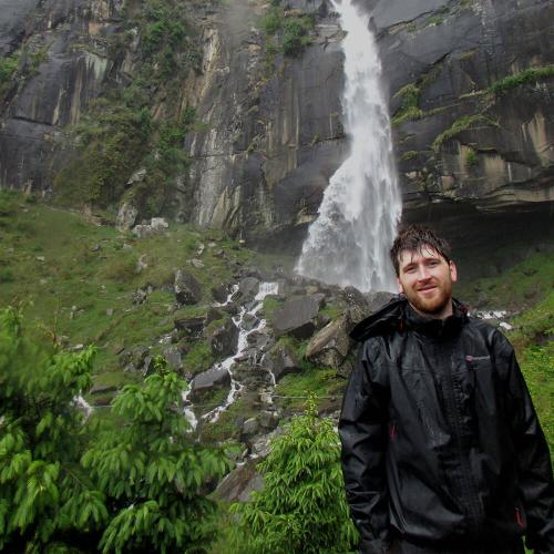 Man stands in front of waterfall