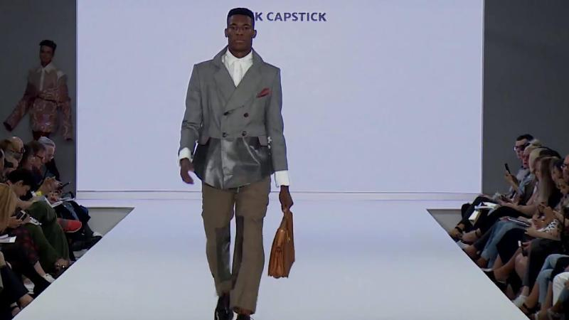 A model walks down the runway wearing a suit and carrying a briefcase2