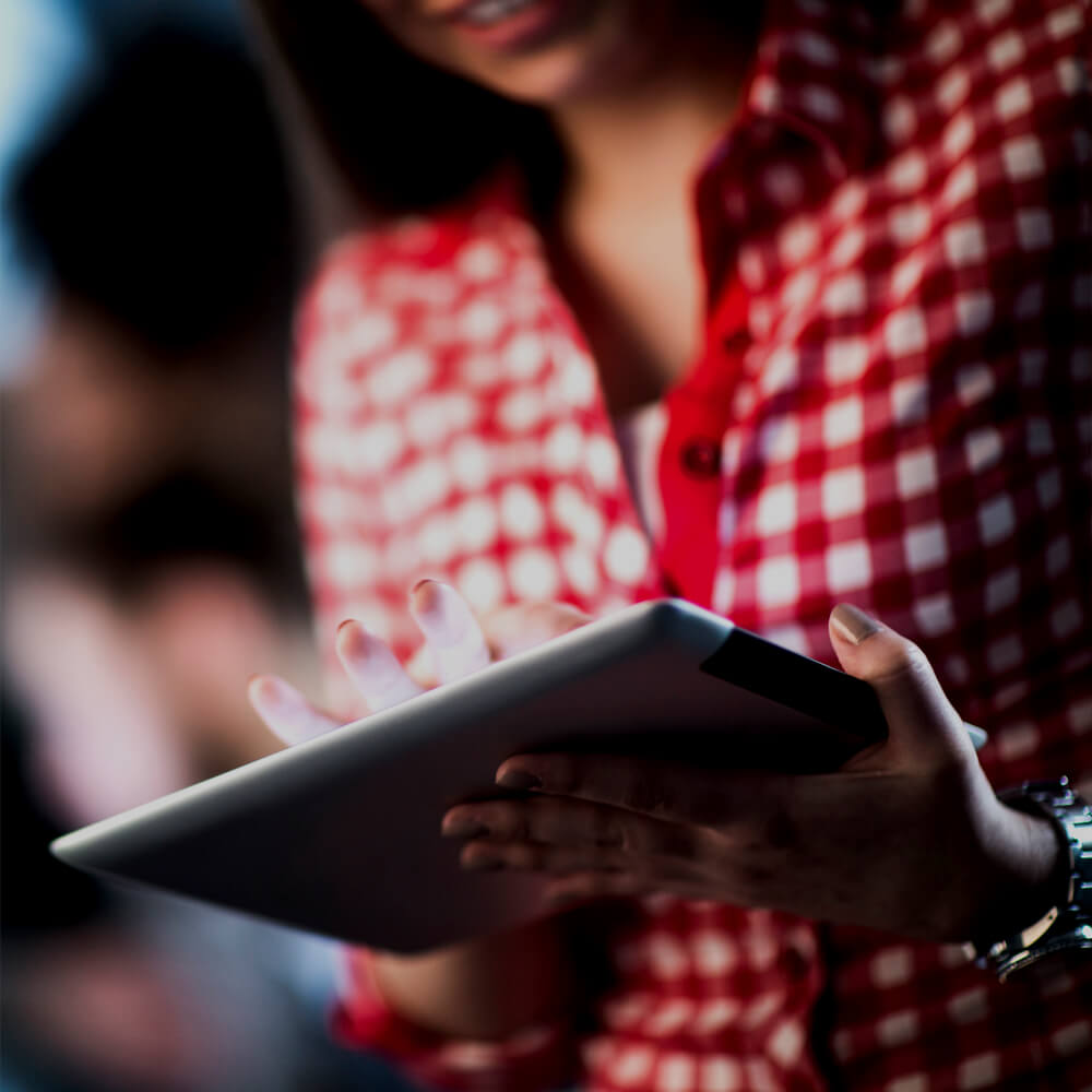 A person in a red and white checked shirt using a tablet2