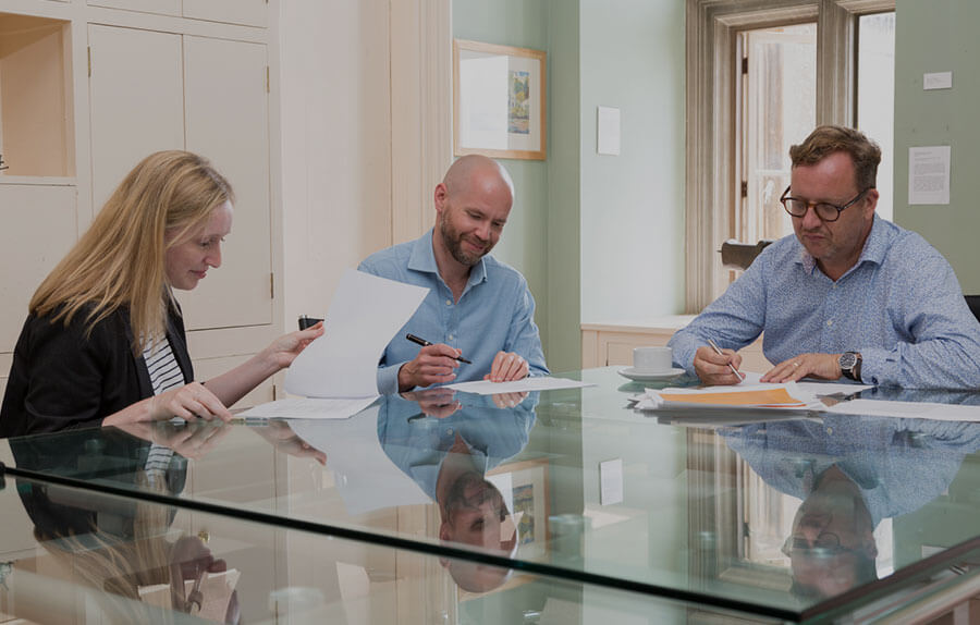 A woman and two men sit around a glass table looking over documents2